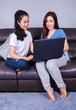 Two woman using a laptop computer on sofa in living room at home. Two young women using a laptop computer on sofa in living room at home Stock Image