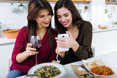 Two young women using mobile phone while eating in the kitchen. Royalty Free Stock Photos