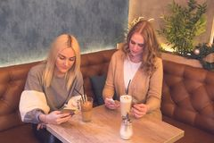 Two young women using mobile phones while drinking coffee in a c royalty free stock photos