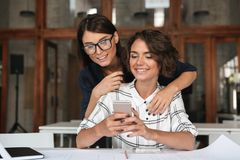 Two young women using smartphone by the table Royalty Free Stock Photo