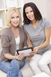 Two Young Women Using Tablet Computer At Home Stock Image