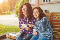 Two young women using tablet computer outdoors. Stock Photo