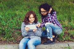 Two young women using tablet computer outdoors. Stock Photos