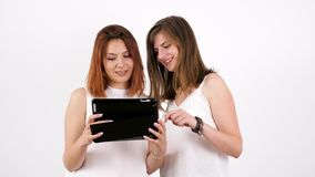 Two young women using a tablet PC and laughing. Over a white wall. Slow motion stock video footage