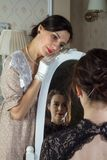Two young women in vintage dresses look at each other through a mirror, a reflection of love. Added a small grain, imitation of stock photo