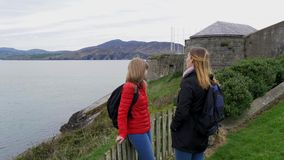 Two young women visit Fort Dunree in Ireland. Travel photography stock video footage
