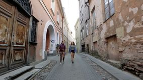 Two young women walking on the narrow streets of Vilnius old town while Talking and laughing.