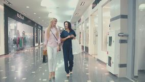 Two young women walk the mall with shopping bags. Shopping stock footage