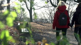 Two young women walk through the park shot from the back. Tourists stop to rest on a wooden bench on a cold day in park stock video footage