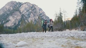 Two young women walking along the coast of rocky river with the backpacks and guitar on the background of the forest and stock video footage