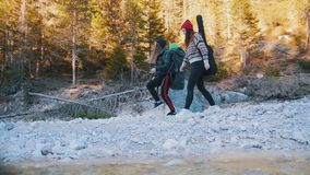 Two young women walking along the rocky path with the backpacks and guitar on the background of the forest stock video