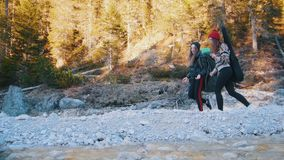 Two young women walking along the rocky path with the backpacks and guitar on the background of the forest and mountain stock footage