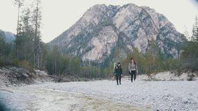 Two young women walking along the rocky shore of the river with the backpacks and guitar on the background of the forest stock video footage