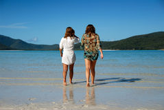 Two young women walking away to sea. Two attractive young women walking away out into a paradise ocean Stock Photo