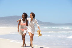Two young women walking barefoot on beach Royalty Free Stock Photos