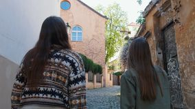 Two young women walking on the narrow streets in the old town
