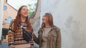 Two young women walking on the narrow streets. Talking and laughing