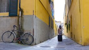 Two young women walking on the narrow yellow streets with luggage stock photography