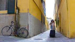 Two young women walking through the narrow yellow streets with luggage stock photo
