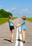 Two young women walking on the road Royalty Free Stock Photo