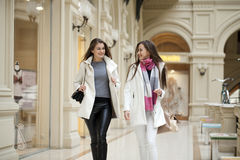 Two young women walking with shopping at the store. Two young brunette girls walking with shopping at the store Royalty Free Stock Image