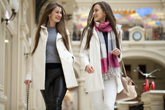 Two young women walking with shopping at the store. Two young brunette girls walking with shopping at the store Stock Image