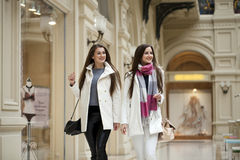 Two young women walking with shopping at the store. Two young brunette girls walking with shopping at the store Stock Photo