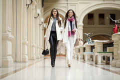 Two young women walking with shopping at the store. Two young brunette girls walking with shopping at the store Stock Photography