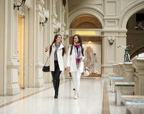 Two young women walking with shopping at the store. Two young brunette girls walking with shopping at the store Royalty Free Stock Photography