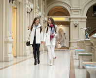 Two young women walking with shopping at the store. Two young brunette girls walking with shopping at the store Stock Images