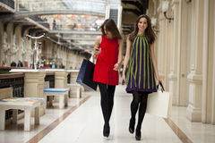 Two young women walking with shopping at the store. Two young brunette girls walking with shopping at the store Stock Photos