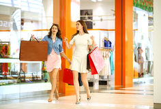 Two young women walking with shopping at the store Royalty Free Stock Images