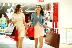 Two young women walking with shopping at the store Royalty Free Stock Photo