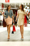 Two young women walking with shopping at the store Royalty Free Stock Image