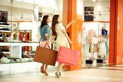 Two young women walking with shopping at the store. Two young girls walking with shopping at the store Royalty Free Stock Images