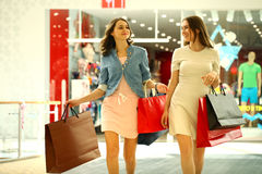 Two young women walking with shopping at the store. Two young girls walking with shopping at the store Stock Photos