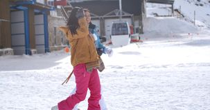Two young women walking through snow at a resort. Two young women walking through snow at a winter ski resort smiling and chatting as they enjoy their vacation stock video footage