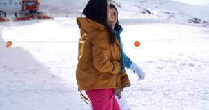 Two young women walking through snow at a resort. Two young women walking through snow at a winter ski resort smiling and chatting as they enjoy their vacation stock footage