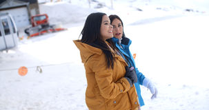 Two young women walking through snow at a resort Royalty Free Stock Images