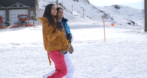 Two young women walking through snow at a resort Stock Photos