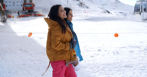 Two young women walking through snow at a resort Stock Images