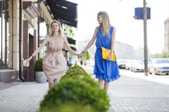 Two young women walking in the summer city Royalty Free Stock Image