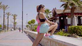 Two young women warming up before exercising. Standing with their feet on a low stone wall stretching their muscles  side view from the rear stock video footage