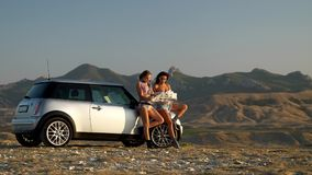 Two young women watch the road map Standing near the car in backdrop of mountain range at the sunset Two seconds later