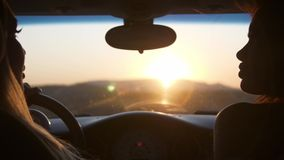 Two young women watch the sunset Sitting in the car Mountains are visible from the car window Wind shakes curls of hair