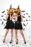 Two young women wearing black dresses, witch hats and high heels hold Halloween pumpkins on their faces stock images