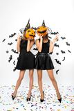 Two young women wearing black dresses, witch hats and high heels hold Halloween pumpkins on their faces royalty free stock photo
