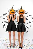 Two young women wearing black dresses, witch hats and high heels hold Halloween pumpkins on their faces royalty free stock photos
