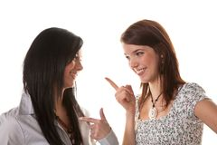 Two young women whisper together Stock Photo