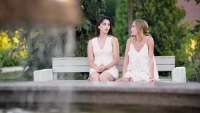 Two young women in white stylish dresses chatting in park sitting on bench. stock video footage